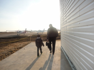 My son walking out to the plane with the pilot.